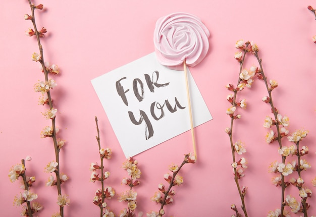 For you handwritten inscription. hand drawn lettering,  calligraphy. card with pink  rose candy in pastel colors on a wooden stick on a grey  background, valentine, mother's day.