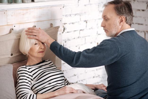 У тебя жар. красивый старший мужчина трогает лоб лежащей жены, чтобы почувствовать жар.
