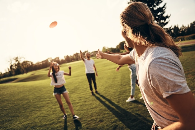 You just have to catch! group of young people in casual wear playing frisbee while spending carefree time outdoors
