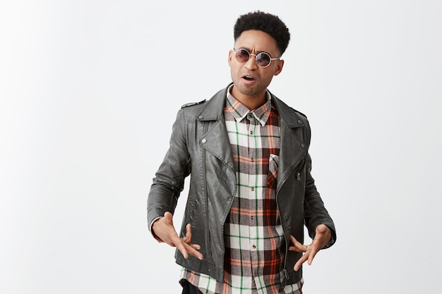 Do you know who i am, man. portrait of angry black-skinned african guy with curly hair in leather jacket and sunglasses gesticulating with hands