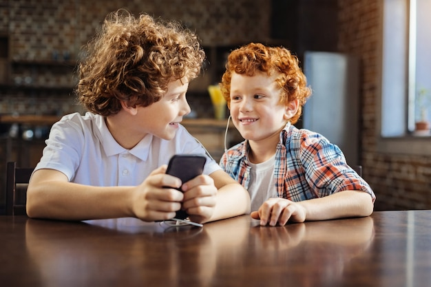 Do you like this one. relaxed little brothers chatting and smiling while both sitting at a table and listening to the music playing.