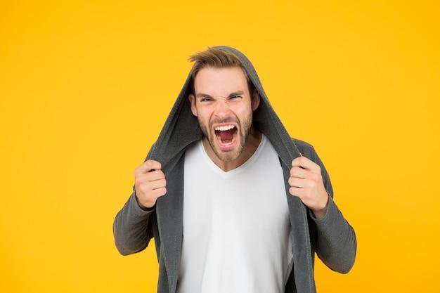 怒らせたな。怒っている人の黄色の背景。怒った気分のハンサムな男。無精ひげを生やしたモデルは怒りで悲鳴を上げます。負のエネルギー。怒りと感情。ワイルドで行こう!
