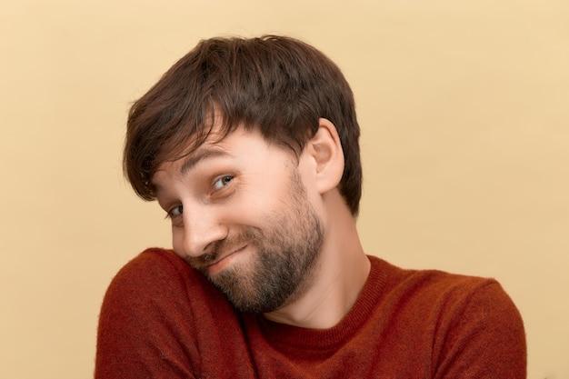 넌 날 부끄럽게 해. 스웨터를 입고 수염을 가진 수줍은 젊은 남자의 사진은 베이지 색 벽에 포즈를 취하고 그의 눈썹 아래에서 보입니다.