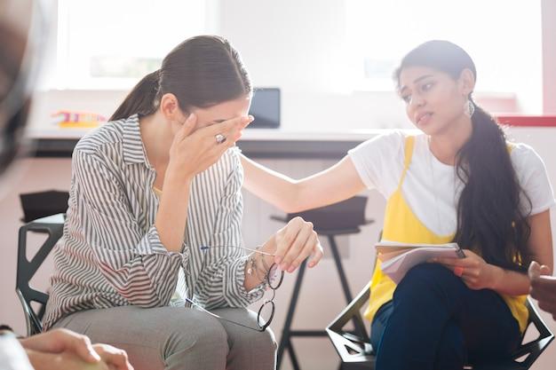 あなたは泣くかもしれません。心理的なセッションで彼女の同僚が彼女の友好的なサポートを示している間、彼女の涙を泣いて隠している動揺した若い女の子