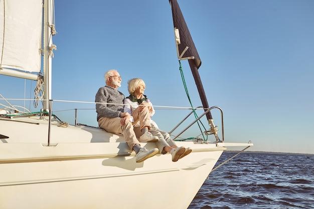 あなたと海穏やかな青い海の帆船の横に座っている幸せな年配のカップル