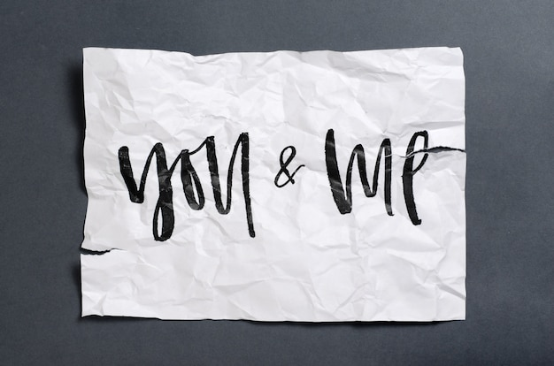 You and me. handwritten text on white crumpled paper.