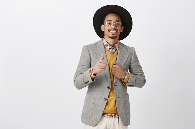 You and me, perfect combination. portrait of confident attractive rich dark-skinned guy in stylish hat and jacket pointing with gun gesture, greeting friends during party