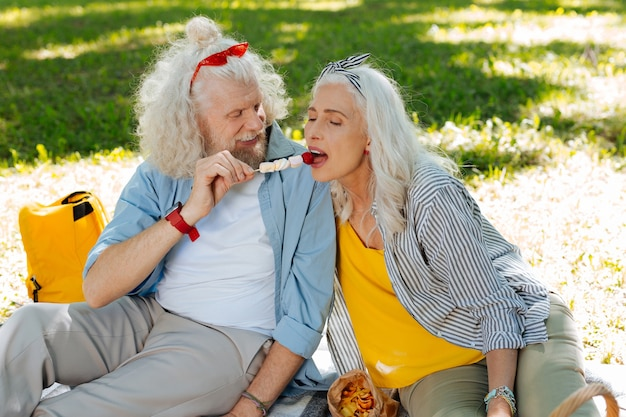 You must try. happy nice man feeding his wife while having a picnic together with her