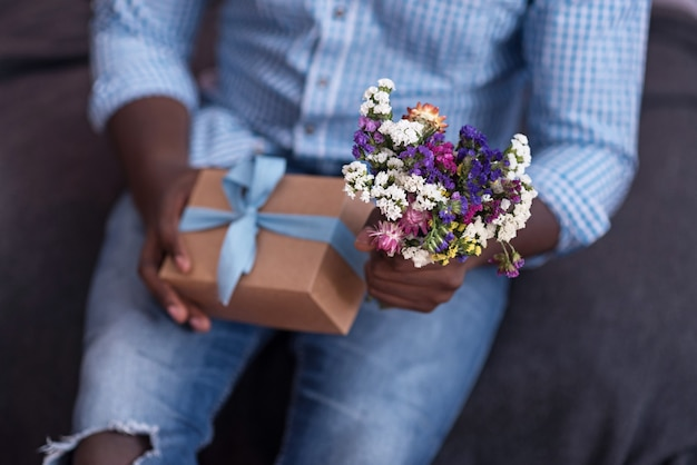 For you my dear. close up of gift and flowers held by african man preparing for giving them to his girlfriend.