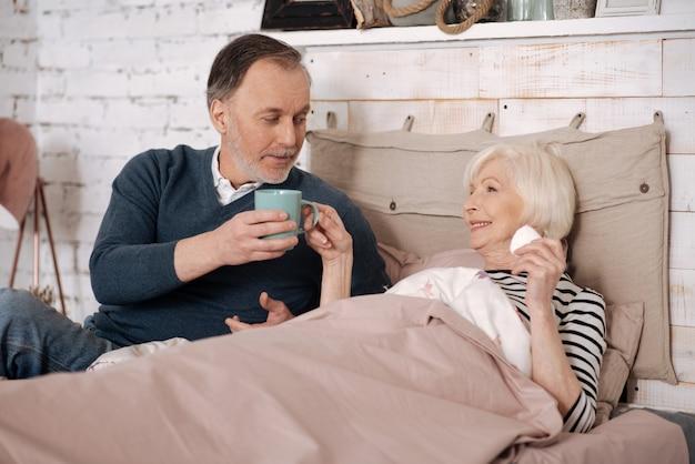 Вы нуждаетесь в этом. старый красавец напоит горячим напитком свою пожилую больную жену, лежащую на кровати, накрытой теплым одеялом.