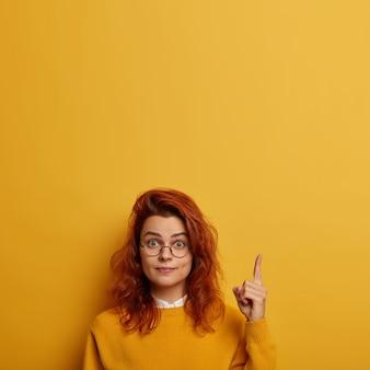 좀 봐. 놀란 빨간 머리 유럽 여성은 둥근 안경을 쓰고, 위의 포인트는 새로운 제품을 보여주고, 복사 공간을 광고합니다.