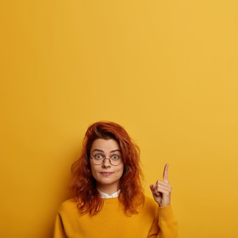 You need look. surprised redhead european woman wears round glasses, points above, shows brand new product, advertises copy space