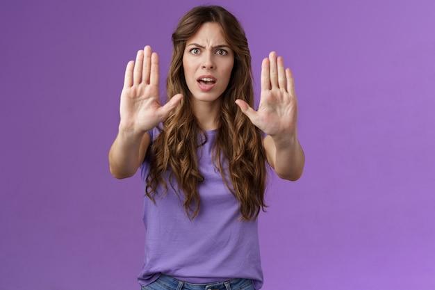 あなたはそれを保持するのをやめる必要があります。真面目そうな強烈な不機嫌な女性が手を引っ張る禁止タブーサイン眉をひそめる要求十分に私を撃つ悪い気分の制限紫の背景を間違えます。
