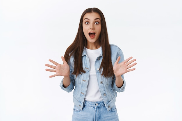 당신은 그것을 믿지 않을 것입니다. 놀라움과 감동을 받은 흥분한 갈색 머리 소녀, 손을 들고 누군가에게 뜨거운 놀라운 소식을 전하는 것처럼 입을 벌리고 놀라고 놀라며 웃고 있습니다.
