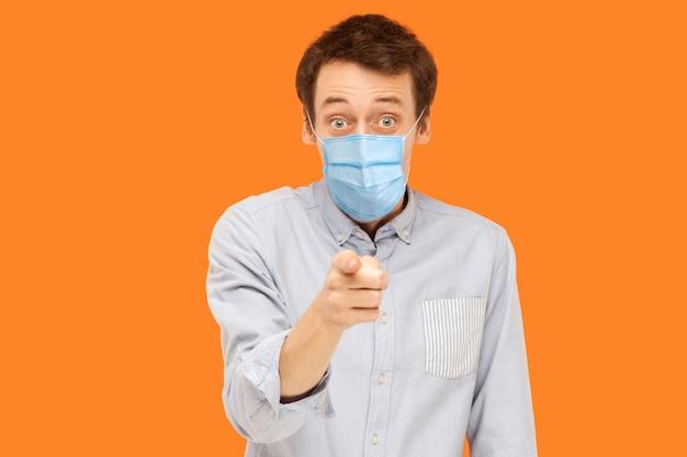 Ты? портрет потрясенного или удивленного молодого работника с хирургической медицинской маской, стоя указывая и глядя на камеру с изумленным лицом и спрашивая. крытая студия выстрел, изолированные на оранжевом фоне.