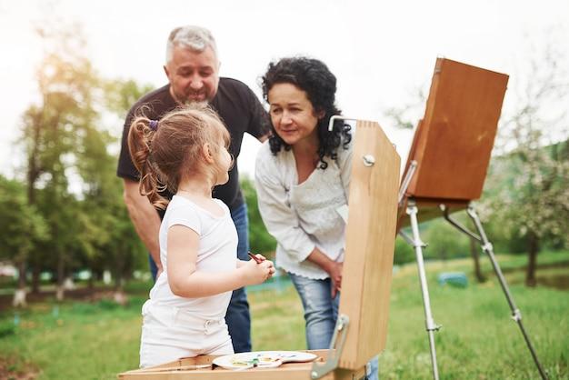 Lo stai facendo bene. nonna e nonno si divertono all'aperto con la nipote. concezione della pittura