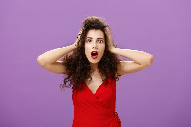 You do not say. portrait of shocked and impressed speechless woman with curly haircut in luxurious evening dress opening mouth from amazement and shock holding hands on head stunned over puple wall.