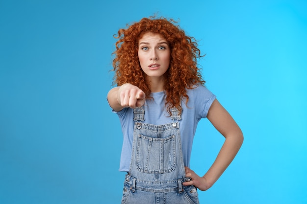 おなじみのようです。心配している心配している活気のある赤毛の感情的な巻き毛の女の子のポインティングカメラは神経質に興奮しているように見えます。コピースペース