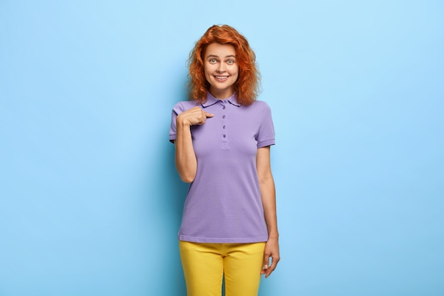 Do you select me? charming red haired female woman points at herself