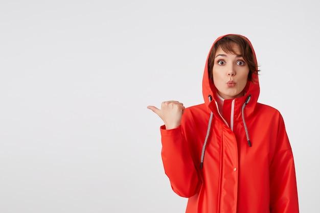 당신은 그것을 봐야합니다! 빨간 비옷에 젊은 귀여운 행복 짧은 머리 여자, 당신의 관심을 끌고 싶어, 복사 공간에 손가락을 가리 킵니다. 서 있는.