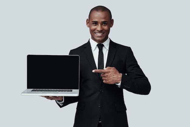 당신은 이것을보아야합니다! 노트북을 가리키고 회색 배경에 서서 웃고 있는 정장 차림의 젊은 아프리카 남자
