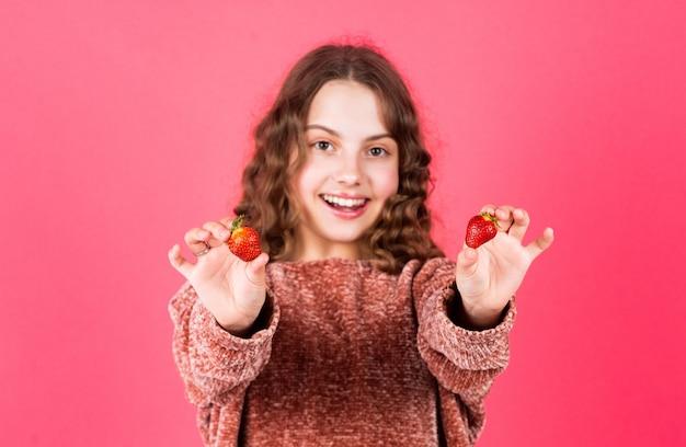 これを試してみてください。イチゴを食べる小さな女の子。健康的なダイエット食品。子供のヘルスケア。小さな子供の健康的な朝食。ダイエットとビタミンの概念。夏のベリーの収穫。子供はイチゴが大好きです。
