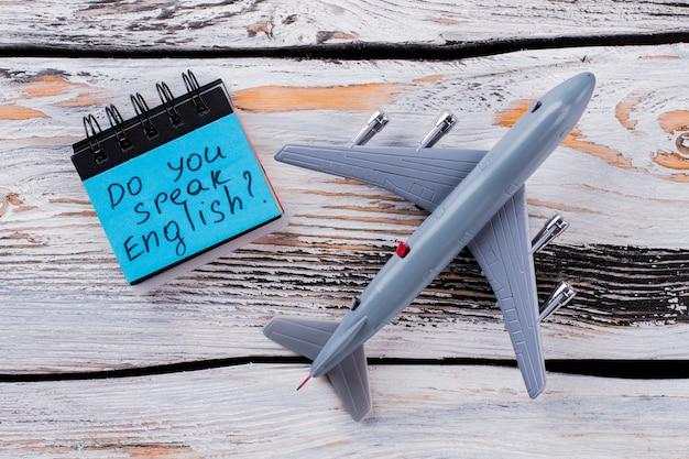 Do you speak english. toy passanger air plane on white wood.