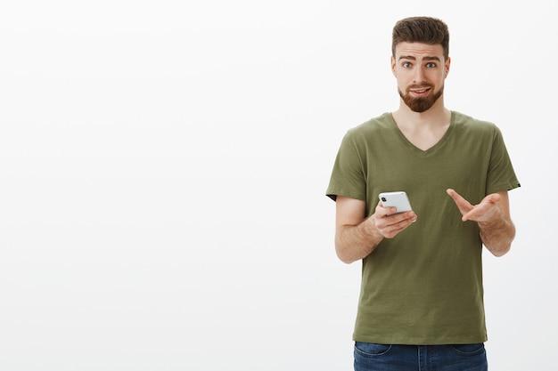 いいアイデアだと思います。スマートフォンを使ってオンラインギフトを購入し、保持デバイスが問題を抱えて不確かに見えることを指して、友人からアドバイスを求めている不確かで躊躇するかわいいひげを生やした彼氏