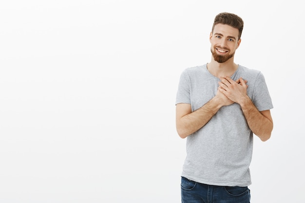 You touched my heart. portrait of handsome stylish and charismatic masculine caucasian brunet with beard holding arms on chest thankful and grateful smiling broadly with sincere love and admiration