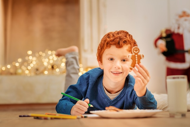 Do you want one. relaxed little boy smiling while holding a home baked gingerbread man and drawing on the floor.