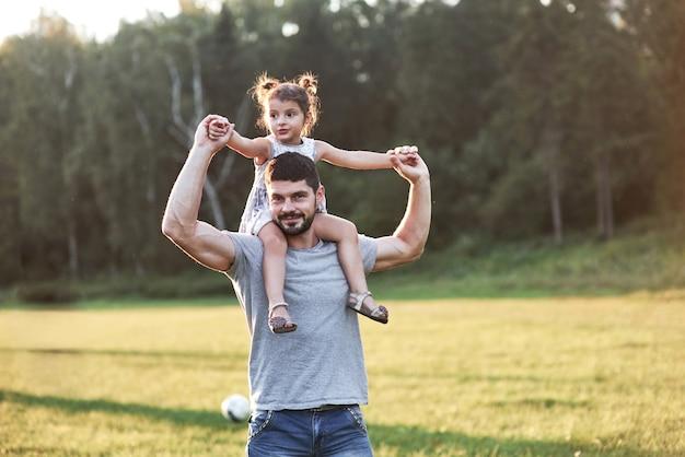 あなたは将来私のように成長するでしょう、しかし今私はあなたを私の肩に乗せさせてください。背景の美しい草や森で彼の娘とお父さんの写真。