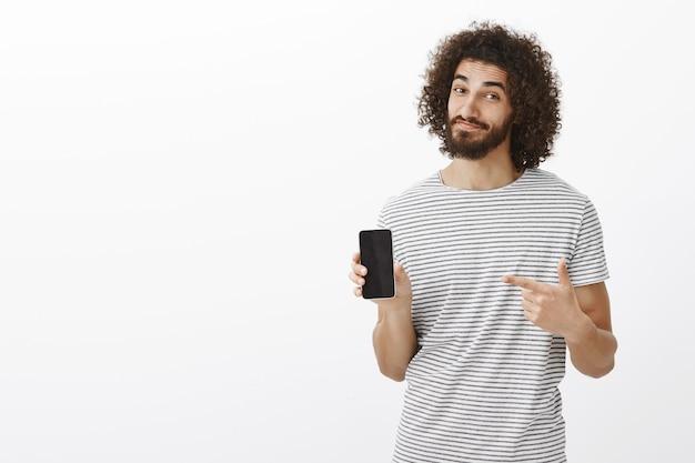 新しい電話を購入しないと後悔します。ひげと巻き毛のハンサムなスタイリッシュなヒスパニック系男性モデルの肖像画