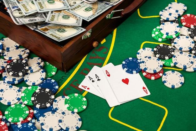 あなたはカジノで勝ちます。ポーカーテーブルにチップとカードが入ったお金の完全なスーツケース