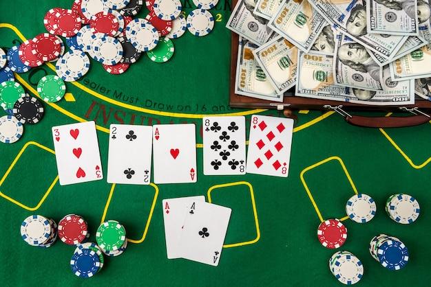Вы выигрываете в казино. полный чемодан денег с фишками и картами на покерном столе