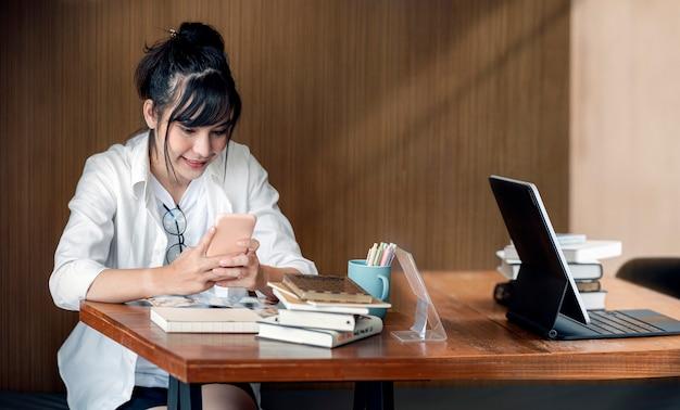 Youg красивая женщина в очках с помощью смартфона с счастьем, сидя в офисной комнате.