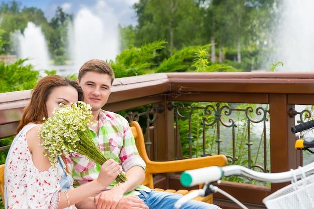 남자 친구와 벤치에 앉아 있는 동안 작은 흰색 꽃의 꽃다발 냄새를 맡는 젊은 여성과 공원에서 맞은편에 자전거를 주차했습니다