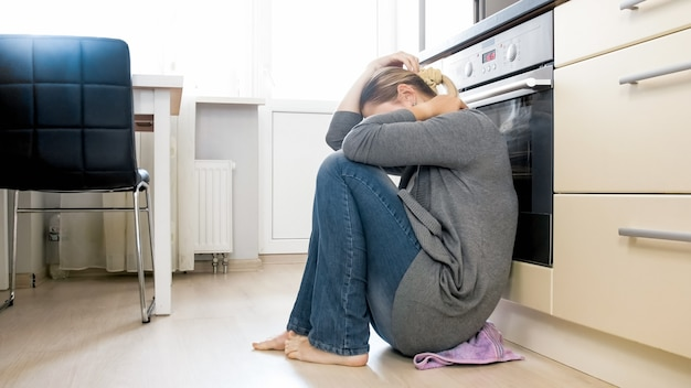 台所の床で泣いている若い女性。家族関係とうつ病の問題。