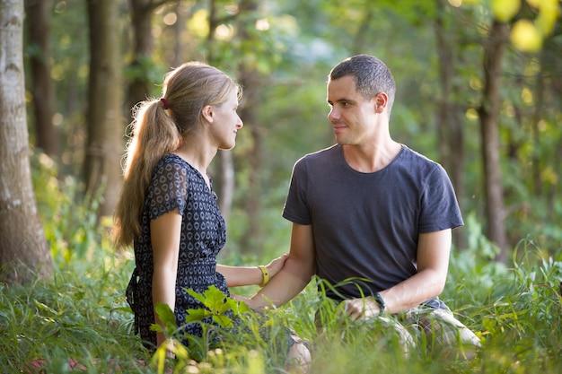 Yougカップル、男と女が一緒に座って自然を楽しんで屋外。