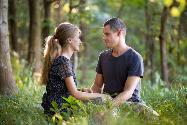 Yougカップルの男性と屋外で自然を楽しんで一緒に座っている女性