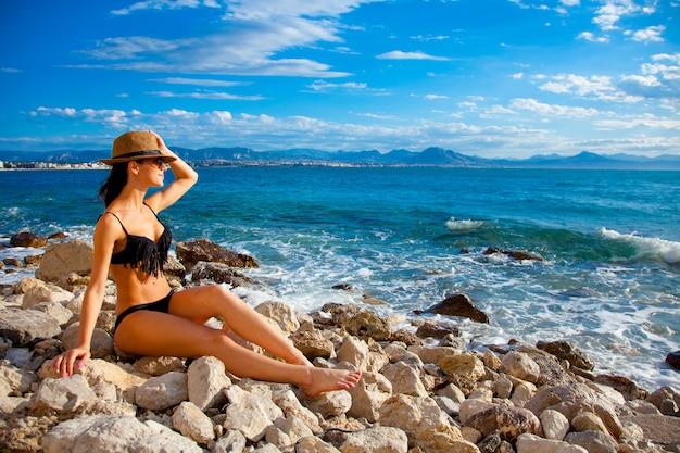 ビーチに座っているビキニのyoug女性