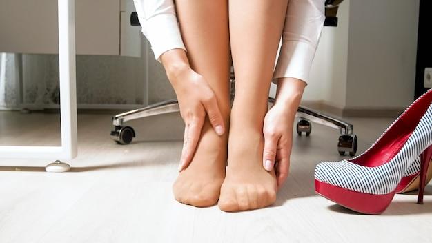 Молодая женщина чувствует боль в ногах и ступнях после тяжелого рабочего дня в офисе.