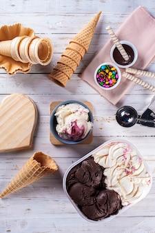 Мороженое yougurt с ягодами и шоколадное мороженое вместе в коробке для доставки. композиция с шишками.