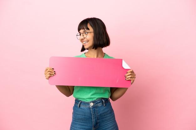 Юная женщина держит пустой плакат и смотрит в сторону