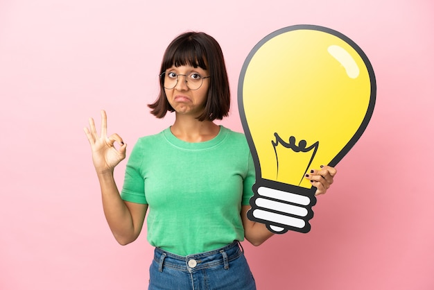 Youing woman holding a bulb icon and doing ok sign