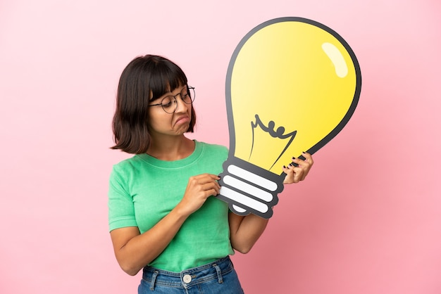 Youing woman holding a bulb icon and having doubts