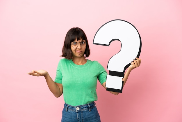 Youing woman holding a question mark icon and having doubts