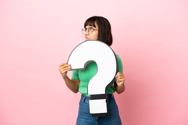 Youing woman holding a question mark icon and looking side