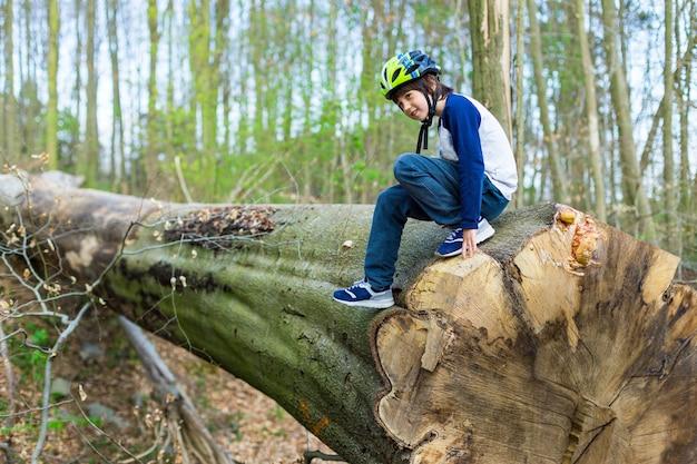헬멧을 쓴 윤의 사랑스러운 소년은 공원에있는 거대한 너도밤 나무의 톱질 한 트렁크에 앉아있다.