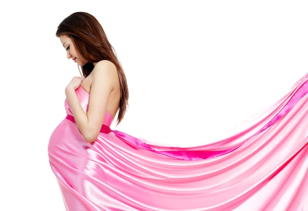 장미 빛 드레스 윤 아름 다운 임신 한 여자-흰 벽