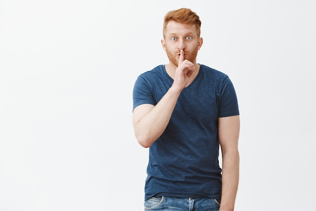 Youn cannot tel anyone, keep it secret. portrait of charming intriguing handsome redhead with bristle, saying shh while showing shush gesture with index finger over mouth, telling rumor to friend